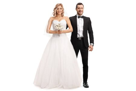 Full length portrait of a beautiful bride and a groom by her side isolated on white
