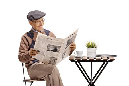 Senior sitting at a coffee table and reading a newspaper isolated on white