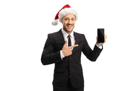 Young man in a suit wearing a Christmas hat, holding a mobile phone and pointing isolated on white background 版權商用圖片