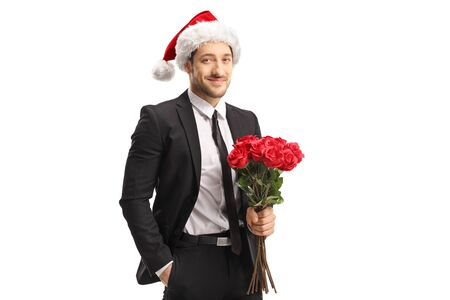 Handsome young man in a suit holding a bunch of red roses for Christmas isolated on white background Stock Photo