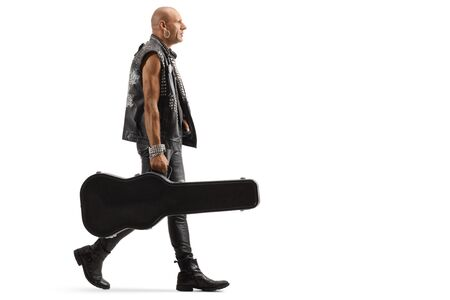 Full length profile shot of a musician in leather clothes walking with a guitar case isolated on white Stok Fotoğraf