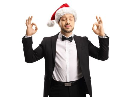 Man in a suit and bow tie wearing a Santa Claus hat and meditating isolated on white