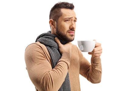 Man suffering a sore throat and drinking a hot tea isolated on white Stock Photo