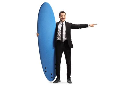 Full length portrait of a man in a suit holding a surfing board and pointing to the side isolated on white