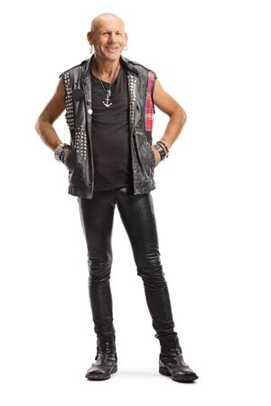 Full length portrait of a punker in leather clothes standing and smiling isolated on white