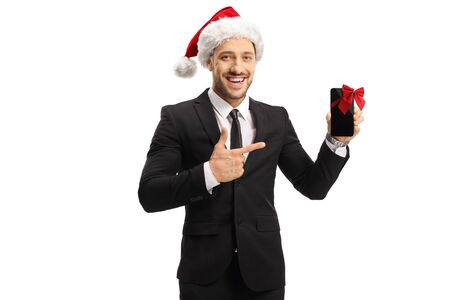 Businessman wearing a santa claus hat pointing on a mobile phone isolated on white