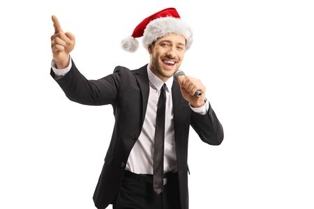 Man wearing a Santa Claus hat singing on a microphone and acpointing up isolated on white background