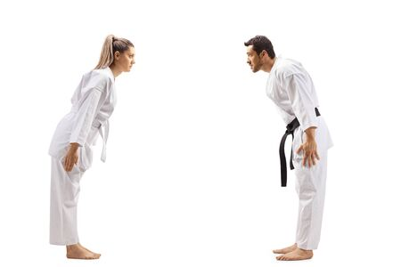 Full length profile shot of a woman with white belt in karate and a man with black belt bowing at each other isolated on white