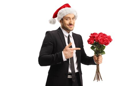 Businessman wearing a Santa Claus hat holding a bunch of red roses and pointing isolated on white background