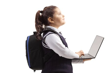 Schoolgirl in a uniform using a laptop computer and looking up isolated on white