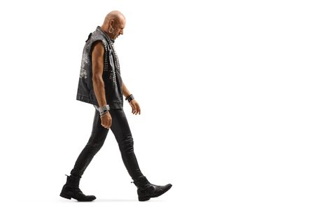 Full length profile shot of a punker walking and looking down isolated on white background