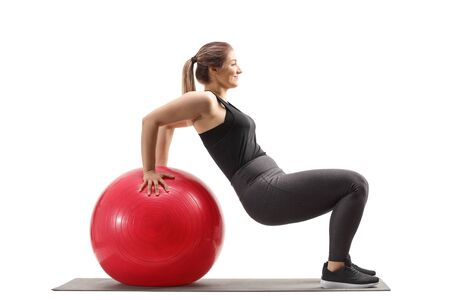 Young woman exercising sit ups with a fitness ball isolated on white background