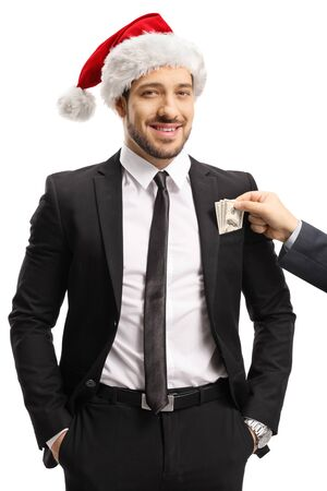 Man putting money into a pocket of a businessman with a santa claus hat isolated on white background Reklamní fotografie