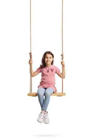Full length portrait of a happy little girl sitting on a wooden swing isolated on white