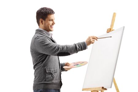 Young man painting on a canvas isolated on white
