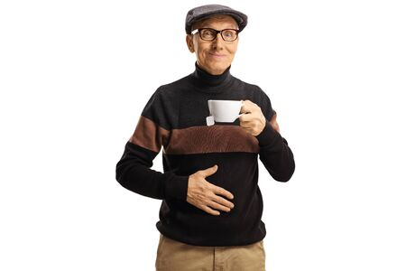Elderly man holding a cup of tea and his hand on his abdomen isolated on white