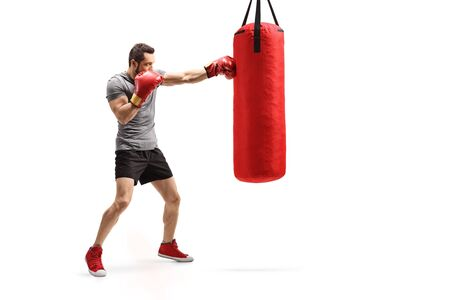 Full length shot of a man punching a bag with boxing gloves isolated on white background Stockfoto