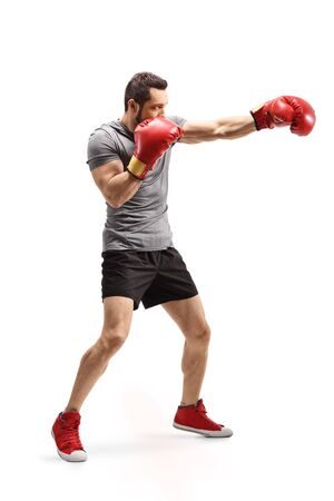 Full length shot of a strong young man punching with boxing gloves isolated on white background