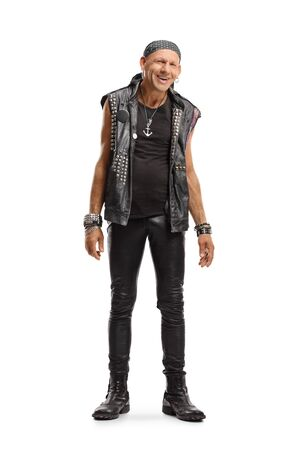 Full length portrait of a happy punker in a leather outfit smiling at the camera isolated on white