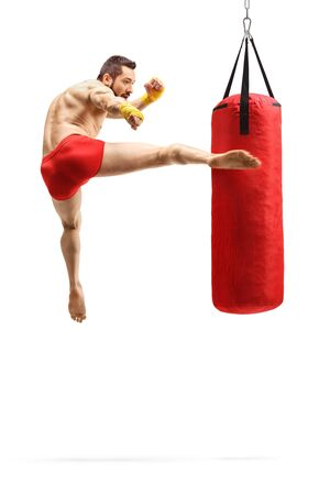 Full length shot of a man exercising kickbox and punching a bag with leg isolated on white background