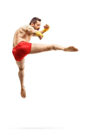 Full length shot of a young male kickboxer performing jumping kick isolated on white Banco de Imagens