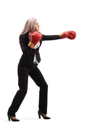 Full length profile shot of a woman in a suit with boxing gloves punching isolated on white background Stock Photo