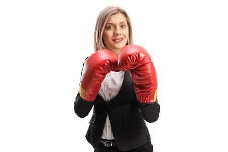 Blond woman in formal clothes wearing red boxing gloves and standing in guard position isolated on white background Stock Photo