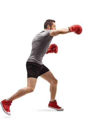 Full length profile shot of a young guy punching with boxing gloves isolated on white background