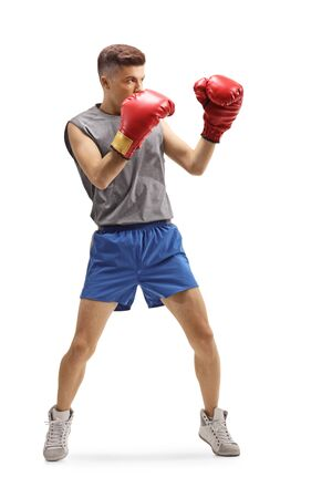 Full length shot of a young guy training boxing with red gloves isolated on white background Imagens