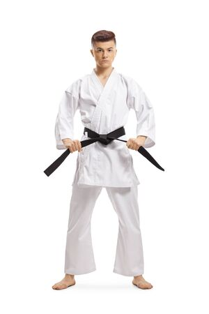 Full length portrait of a teenage boy in karate kimono holding his black belt isolated on white background
