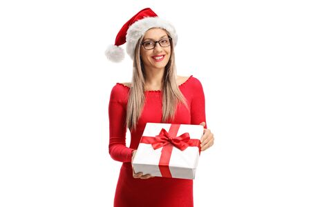Beautiful young woman with a Santa Claus hat holding a Christmas present isolated on white background 写真素材