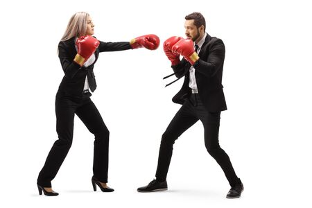 Full length profile shot of a businessman and businesswoman in sparring with boxing gloves isolated on white background