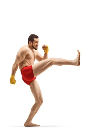 Full length profile shot of a fit man exercising kickboxing and pushing with his leg isolated on white