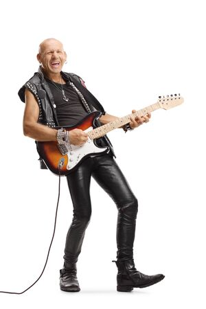 Full length portrait of a male guitarist in leather clothes playing and singing isolated on white background