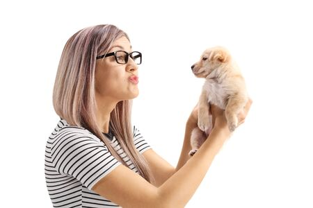 Young woman blowing a kiss to a little puppy dog isolated on white background