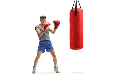 Full length shot of a young guy punching with boxing gloves in a red hanging bag isolated on white background