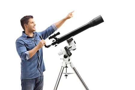 Youn man standing next to a telescope and pointing up isolated on white background Stok Fotoğraf