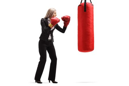 Full length shot of a businesswoman with red boxing gloves exercising with a punching bag isolated on white background Stock Photo
