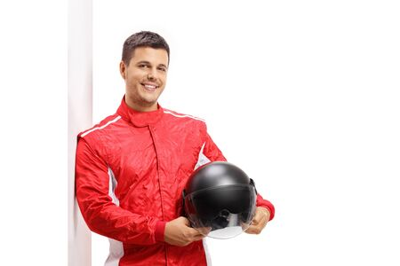 Car racer holding a helmet and leaning against a wall isolated on white background
