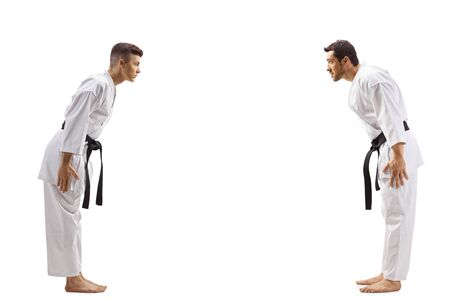 Full length profile shot of young men in karate kimonos bowing to each other isolated on white Фото со стока