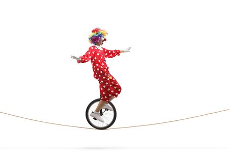 Full length profile shot of a scared clown riding a unicycle on a rope isolated on white background
