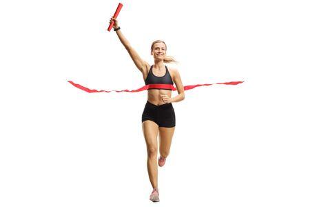 Retrato de cuerpo entero de una mujer atleta terminando una carrera de relevos con un bastón en la mano aislado sobre fondo blanco. Foto de archivo