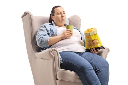 Overweight woman sitting in an armchair eating junk food isolated on white background