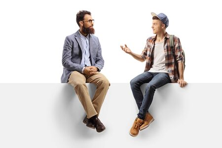 Full length shot of a bearded man and a teenage male student sitting on a panel and talking isolated on white Banco de Imagens