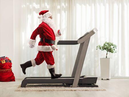 Tiro de perfil de longitud completa de Santa Claus corriendo en una cinta en casa
