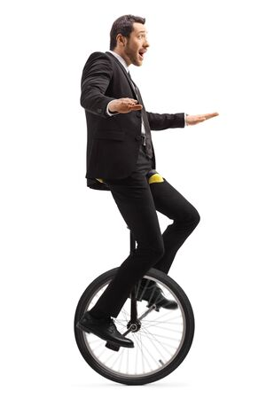 Full length shot of a suprised businessman riding a mono-cycle isolated on white background Stockfoto