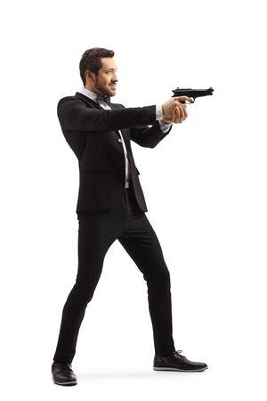 Disparo de longitud completa de un hombre en un traje apuntando con una pistola aislado sobre fondo blanco. Foto de archivo