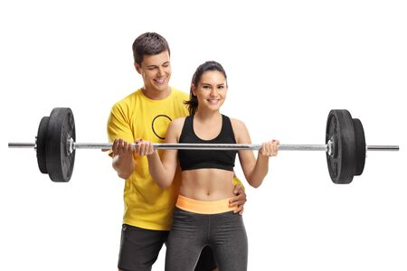 Young woman lifting a barbell with the help of a fitness coach isolated on white background