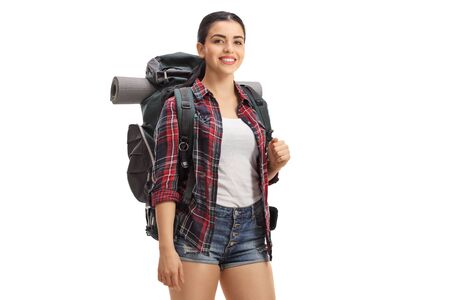Young female hiker with backpack smiling at the camera isolated on white background