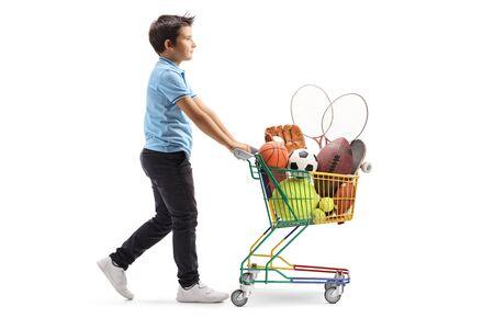 Colpo di profilo a tutta lunghezza di un ragazzo che cammina e spinge un mini carrello con articoli sportivi isolati su sfondo bianco Archivio Fotografico